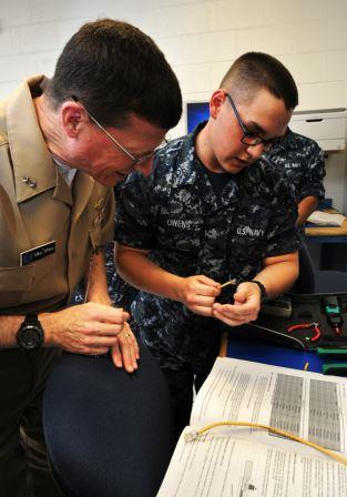 Commander, Naval Education and Training Command (NETC), Rear Adm. Michael S. White, received a quick tutorial from Seaman Recruit Vincent Owens, 19, of Frenchville, Pa., on assembling new Ethernet cables during his first official visit to CID. (U.S. Navy photo by Gary Nichols/Released)
